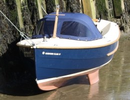 Clam 17 moored at low tide with spray hood on